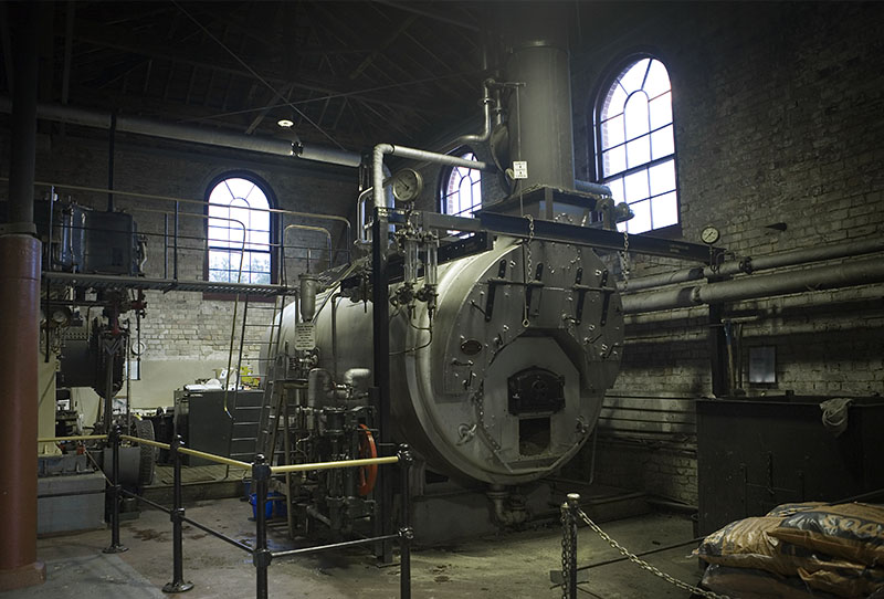 Machine room of an office building (<a href=https://commons.wikimedia.org/wiki/File:19th_century_heat_machine_room_with_coal_boiler,_Auckland_-_0951.jpg>Source</a>)